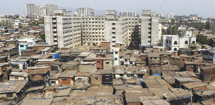 High-rise residential buildings are seen behind a cluster of houses at a slum in Mumbai.