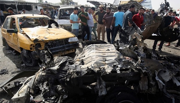 Iraqis check the damage after a suicide bomber detonated an explosives-rigged vehicle in northern Ba