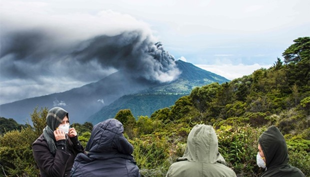 People look at the volcano as it spewes ashes