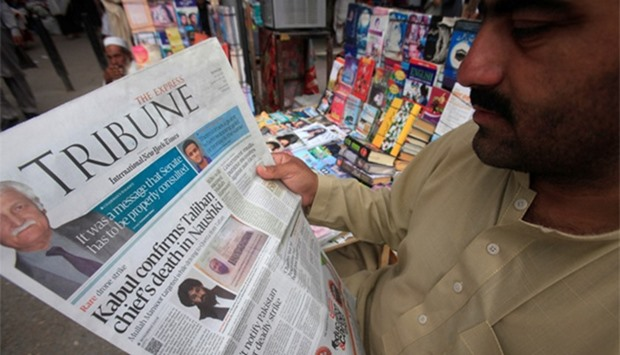 A man reads a newspaper containing news about the death of Afghan Taliban leader Mansour