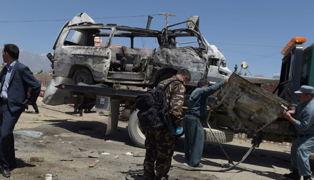 Afghan security personnel stand near damaged vehicles at the scene of a suicide bomb attack