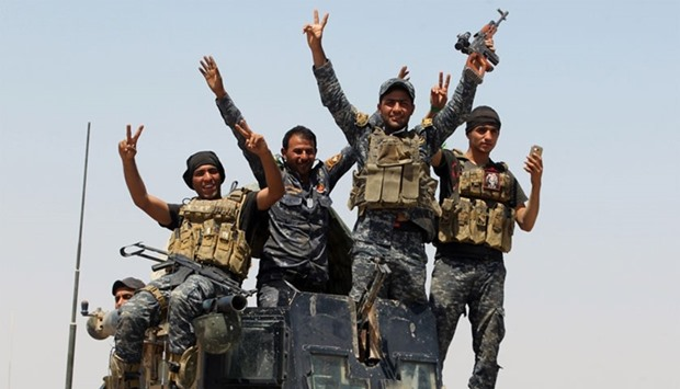 Pro-government forces fighters celebrate in the al-Sejar village, in Iraq's Anbar province.