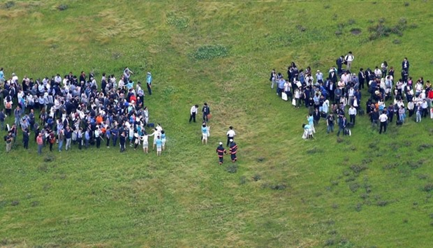 An aerial picture shows passengers after they escaped from a Korean Air Lines plane whose engine had