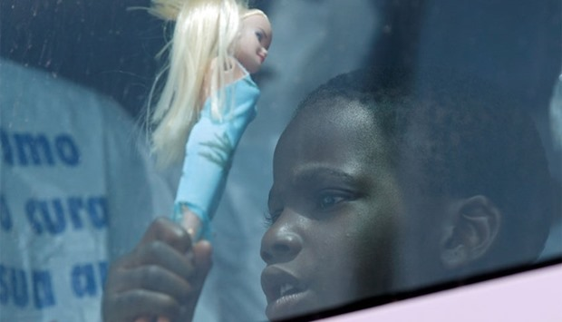 A child holds a doll as he sits in a coach after disembarking from the Italian Navy vessel Vega at t