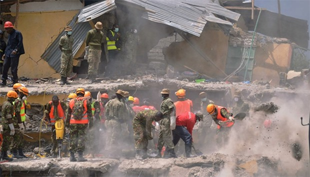 Rescue and medical personnel try to free a woman (unseen) who discovered alive in Nairobi after bein