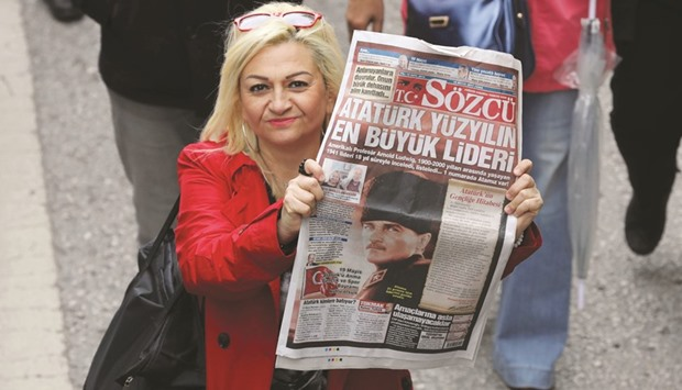 A woman holds up a copy of Sozcu after the ultra-secularist daily came under investigation by Istanb