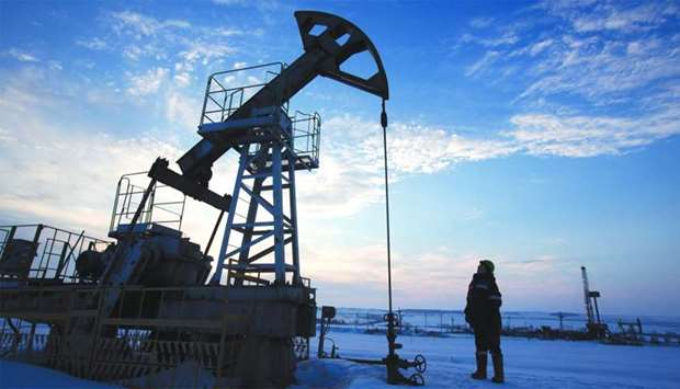 An oil worker inspects a pumping jack in an oilfield operated by Bashneft in Otrada