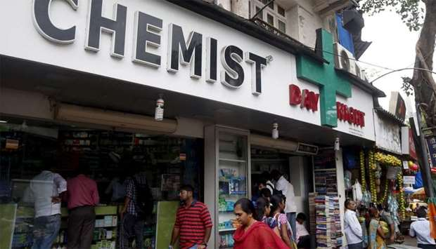 People walk past a chemist shop in Mumbai