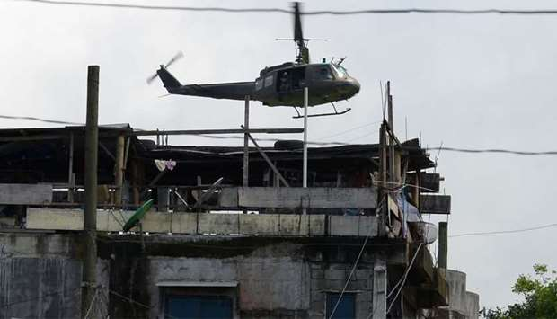 A military helicopter flies past houses in Marawi on the southern island of Mindanao