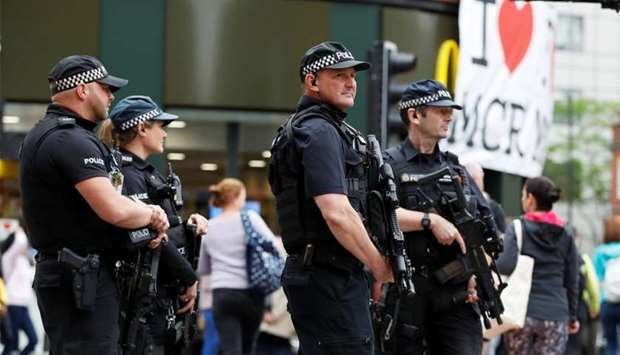 Armed police officers stand on duty in central Manchester