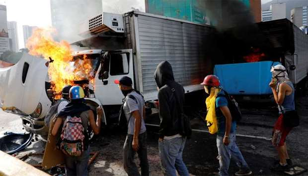 Demonstrators near trucks, which have been set on fire while clashing with riot security forces