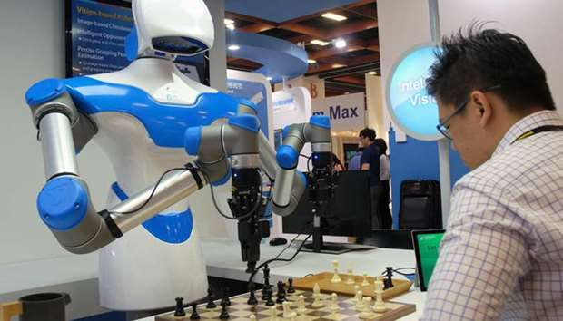A visitor plays chess with a robot designed by Taiwan's ITRI during the Computex Show