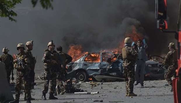 Afghan security forces personnel are seen at the site of a car bomb attack in Kabul