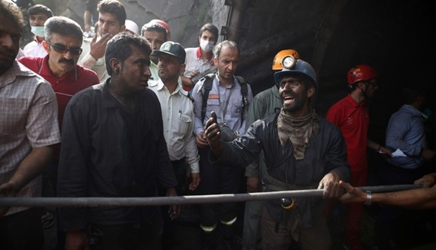 Coal miners and rescue workers gather at the scene following an explosion in a coal mine in Azadshah