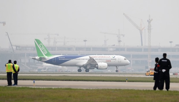 A Chinese C919 passenger jet taxis after landing on its first flight at Pudong International Airport