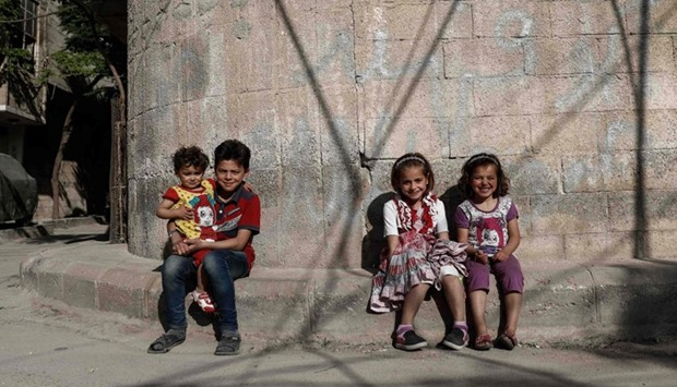 Syrian children pose for a photo near their house in the rebel-held town of Douma, on the eastern ou