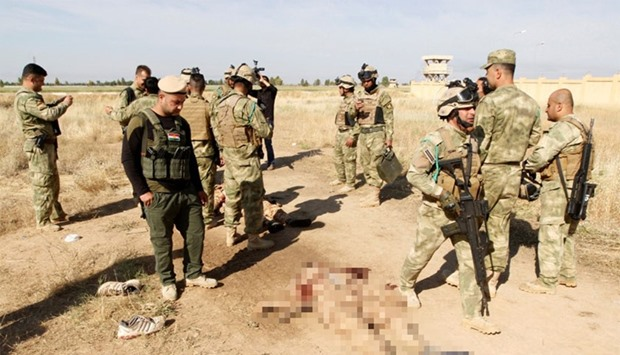 Kurdish peshmerga forces stand near the bodies of suicide bombers of Islamic State, in the city of K