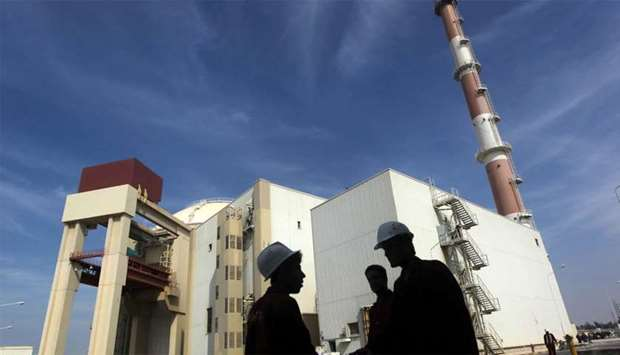 Iranian workers stand in front of Bushehr nuclear power plant 1,200 km south of Tehran