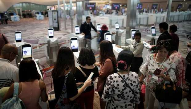 Passengers line-up at automated immigration control gates at Changi airport's Terminal 4 in Singapor