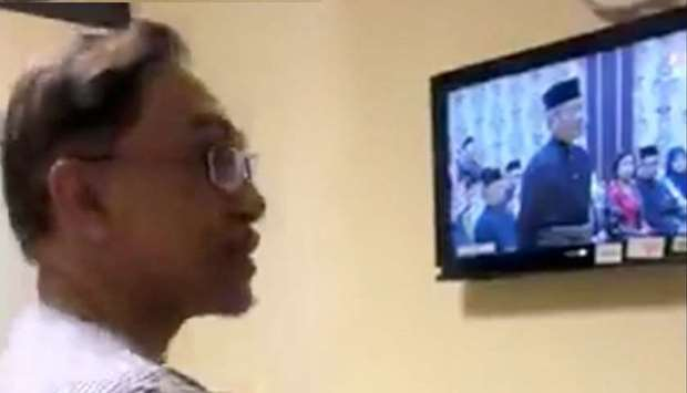 Malaysian political leader Anwar Ibrahim watches a live broadcast of the swearing in ceremony of new