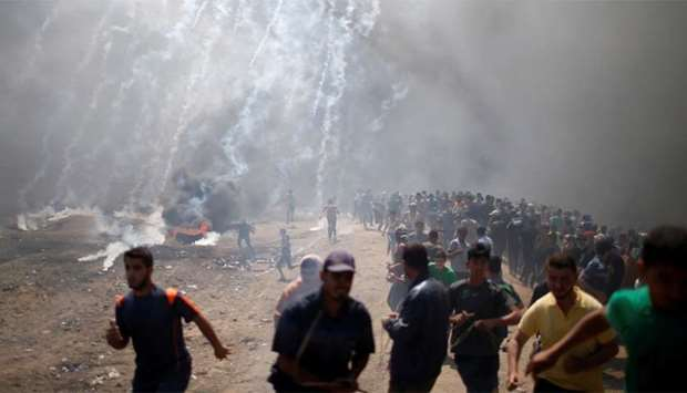 Palestinian demonstrators run from tear gas fired by Israeli troops during a protest