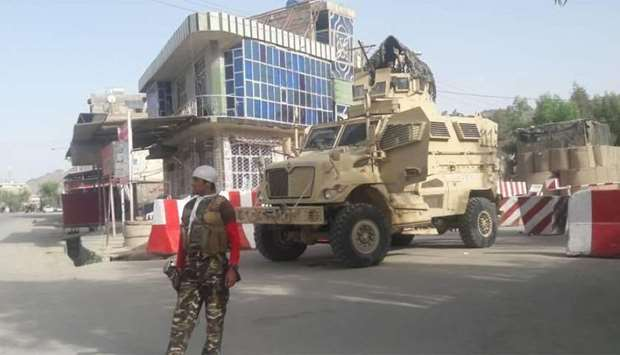 An Afghan security force personnel stands guard at the entrance gate of the government compound of F
