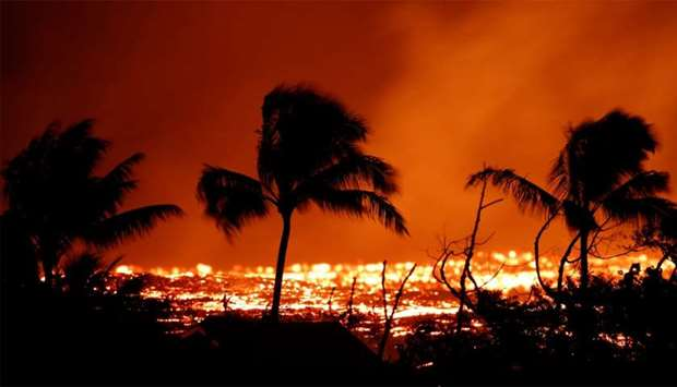 Lava flows past trees on the outskirts of Pahoa during ongoing eruptions of the Kilauea Volcano in H