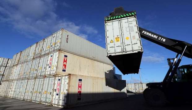 An employee uses a crane to lift container in Port Stanley