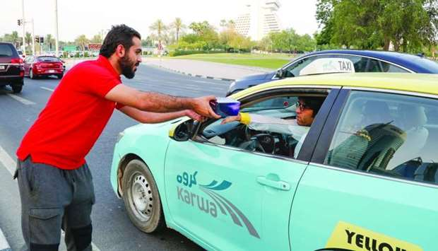A taxi driver receiving an Iftar box from an Ooredoo volunteer.