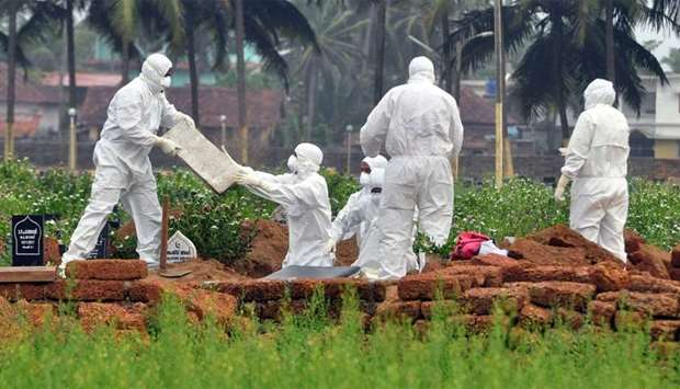 Doctors and relatives wearing protective gear dig a grave to bury the body of a victim, who lost his