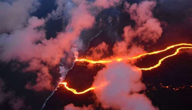 Lava flows are seen entering the sea along the coastline during ongoing eruptions of the Kilauea Vol