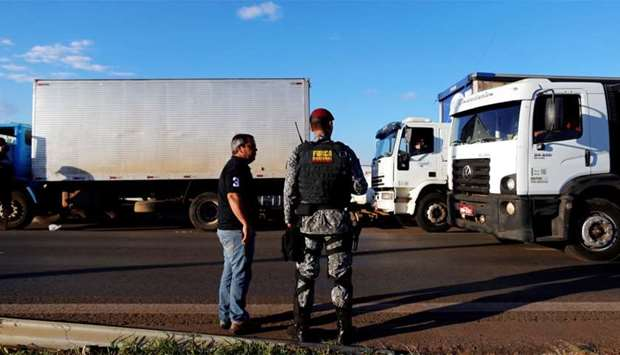 A police officer take position as they order truckers to clear the blocked BR-04 highway in Luziania