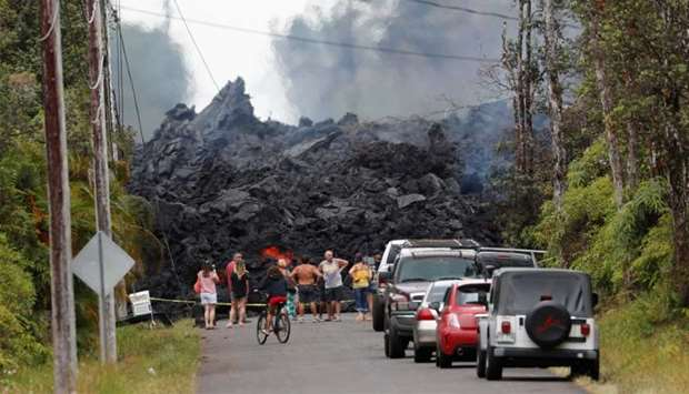 Onlookers gather in front of a fresh lava flow from the Kilauea volcano, in the Leilani Estates near