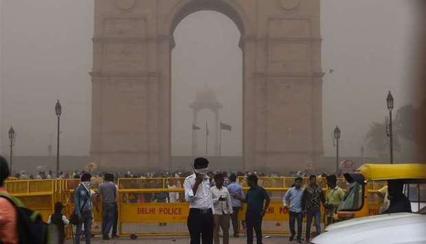 An Indian traffic policeman covering his face as he stands on duty during a dust storm in New Delhi