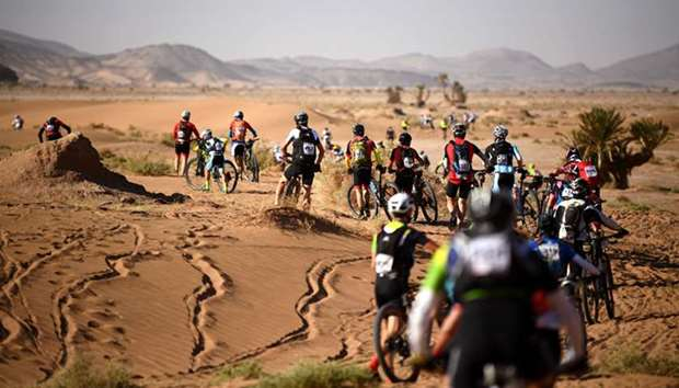 Competitors push their bikes along a sand dune during Stage 4 of the 13th edition of the Titan Deser