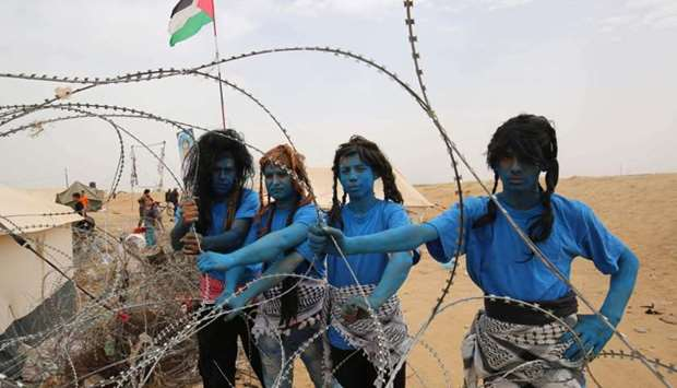 "Palestinians with their faces painted like characters from the movie ""Avatar"" pose for a picture dur"