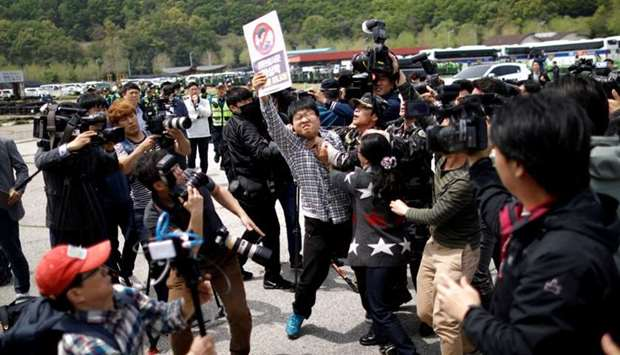 A North Korean defector tries to take an activist who opposes releasing balloons containing leaflets