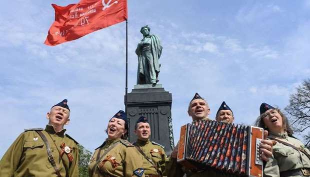 People dressed in Soviet army uniforms sing in front of a monument of poet Alexander Pushkin an hour