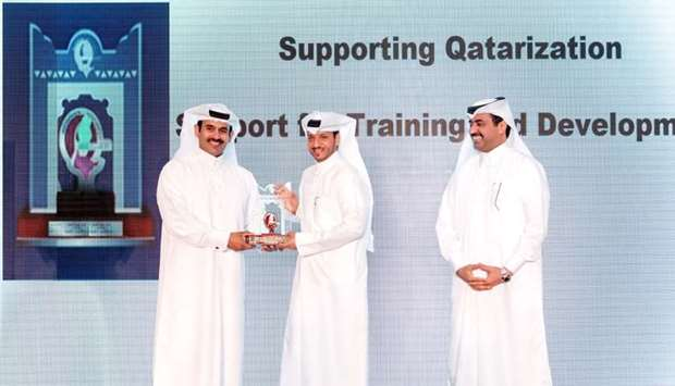 Al-Sulaiti (centre) receives the award from al-Kaabi as HE al-Sada look on