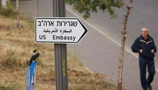 A man walks next to a road sign directing to the US embassy, in the area of the US consulate in Jeru