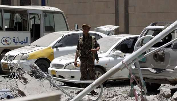 Yemenis check the site of air strikes at the president office in the capital Sanaa