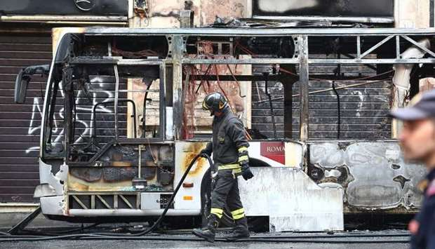 A firefighter walks next to a burned bus in downtown Rome