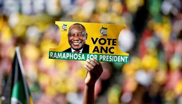 A supporter holds a placard with the face of President of South Africa's governing African National