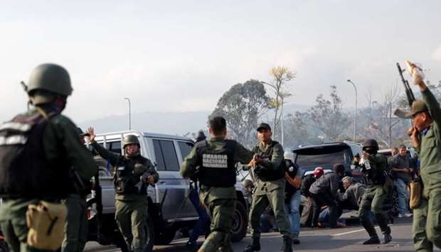 Soldiers and people react to the sound of gunfire near the Generalisimo Francisco de Miranda Airbase