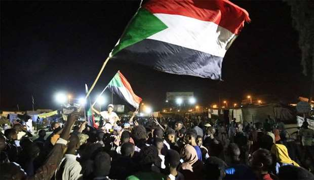 Sudanese protestors celebrate after an agreement was reached with the military council to form a new