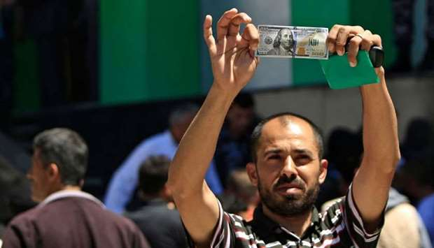A Palestinian man displays a 100 dollar bill, part of $480 million in aid allocated by Qatar, in Gaz