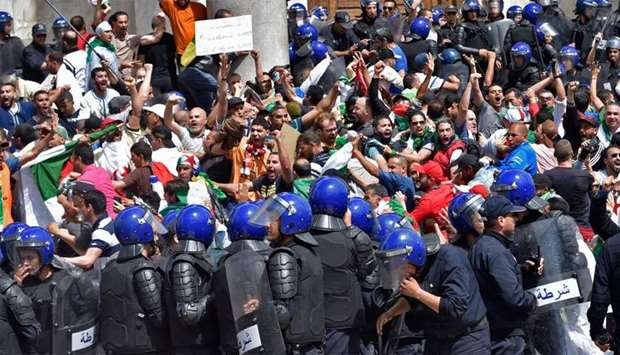 Algerian protesters scuffle with riot police during an anti-government demonstration outside La Gran