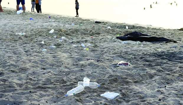 Small pieces of charcoal and plastic bottles leave Mesaieed Beach darker and dirtier.