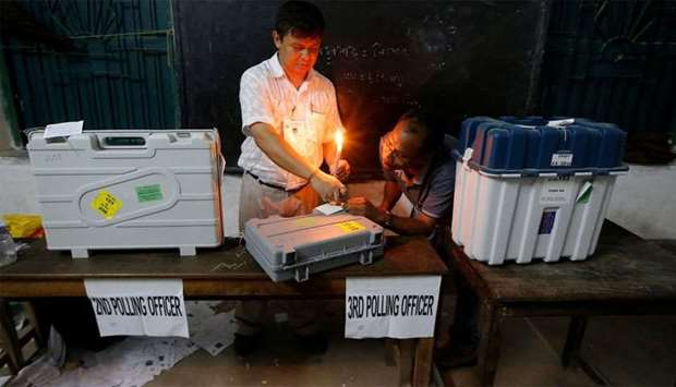 Polling officials seal EVM and VVPAT machines at a polling station after the end of the last phase o