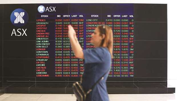 A woman takes a photograph as an electronic board displays stock information at the Australian Secur